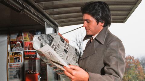 """Harry Meier (Christian Quadflieg), der Protagonist von """"Zwei Flugkarten nach Rio"""", ist ein raffinierter Juwelendieb. Er steht an einem Kiosk und blickt in eine Zeitung."""