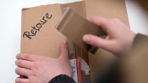 Eine Frau klebt ein Paket mit der Aufschrift Retoure mit Paketband zu.