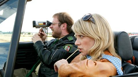 Dietmar Schäffer (Bjarne Mädel, l.) macht begeistert Radarkontrollen am Ortseingang von Hengasch, Sophie Haas (Caroline Peters, r.) ödet die sinnlose Aktion an.