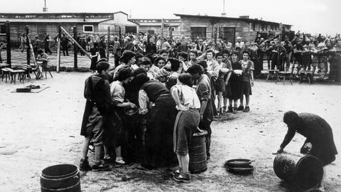 Frauen im Konzentrationslager Gusen bei Linz stehen Schlange für eine Schüssel voll Suppe. Aufnahme von 1945.