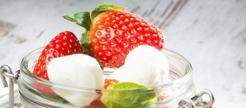 Erdbeeren mit Mozzarella und Basilikum liegen in einem Einmachglas auf einem Tisch.