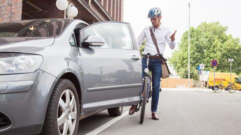 Ein junger Mann beschwert sich über eine offene Autotür, wegen der er beinahe einen Unfall gehabt hätte.