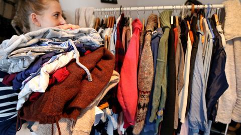 Eine junge Frau hat einen Berg an Wäsche aussortiert und läuft damit an einer vollen Kleiderstange vorbei.