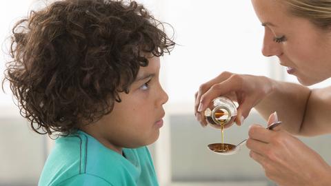Eine Mutter gibt ihrem Sohn einen Löffel voll Medizin.