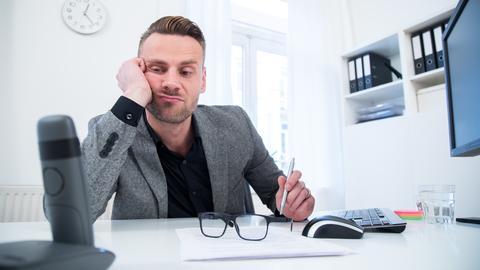 Ein junger Mann schaut in einem Büro gelangweilt und genervt auf sein Telefon, weil niemand anruft.