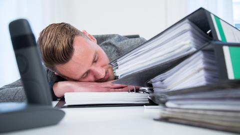 Ein junger Mann schläft in einem Büro am Schreibtisch neben einem Stapel Unterlagen.