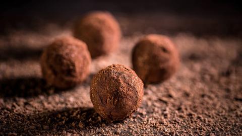 Vier Schokoladenkugeln an dunklem Hintergrund.