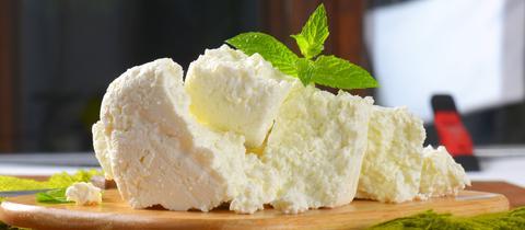 Ein Haufen von krümelig weißem Käse auf hölzernem Schneidebrett.