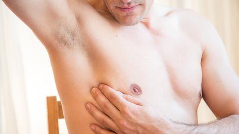 Ein Mann untersucht seine Brust.