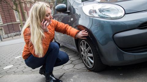 Eine junge Frau inspiziert einen Lackschaden an ihrem Auto und telefoniert dabei.