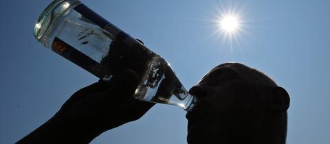 Mann trinkt unter sengender Sonne aus einer Wasserflasche