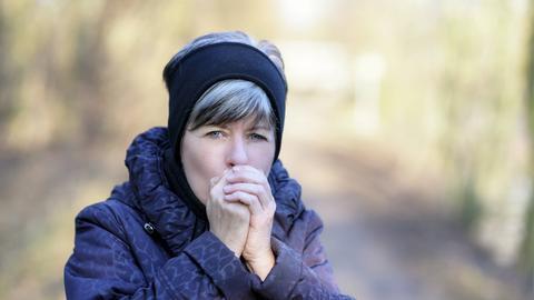 Eine Frau wärmt sich die Hände in der Kälte