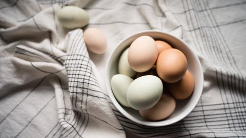 Weiße und braune Eier in einer hellen Schüssel auf einem karrierten Handtuch.