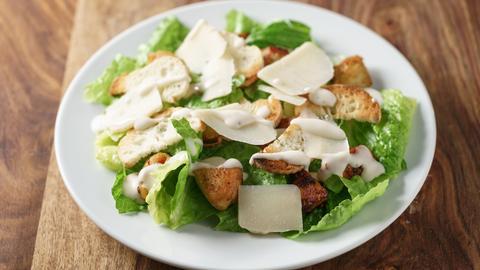 Caesar Salat mit Hühnchen, Käse und Croutons auf einem Teller auf Holztisch.