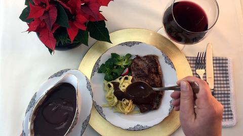 Schokoladensauce wird über einen Teller mit Spätzle, Feldsalat und Steak gegossen.