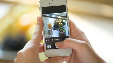 Eine Frau macht mit dem Mobiltelefon ein Foto einer Obstschale.
