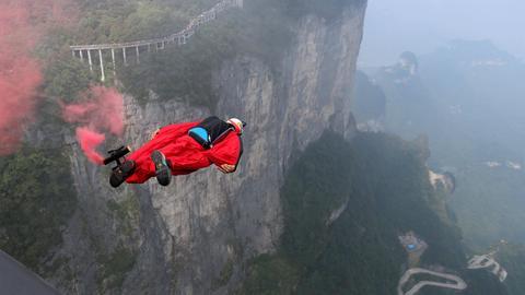 Eine Basejumper springt in einem Wingsuit von einer Klippe und gleitet in das Tal.