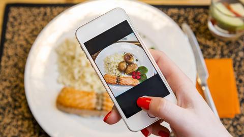Eine Frau fotografiert ihr Essen.