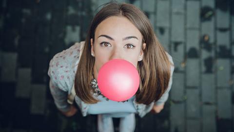 Eine junge Frau macht eine Blase mit einem Kaugummi.