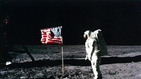 NASA-Originalaufnahme von Edwin Aldrin auf dem Mond neben einer amerikanischen Flagge.