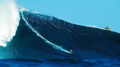 Ein Surfer auf einer riesigen Welle.