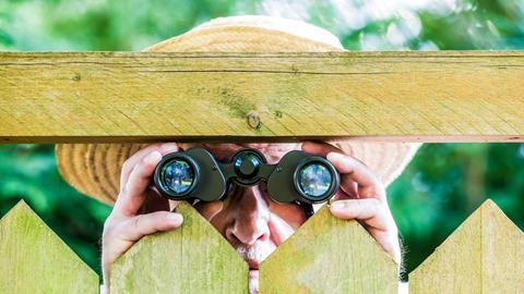 Ein neugieriger Nachbar mit einem Fernglas schaut über den Bretterzaun aus Holz.
