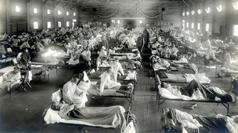 Patienten, die an der Spanischen Grippe erkrankt sind, liegen in Betten eines Notfallkrankenhauses im Camp Funston der Militärbasis Fort Riley in Kansas (USA) (Aufnahme von 1918).