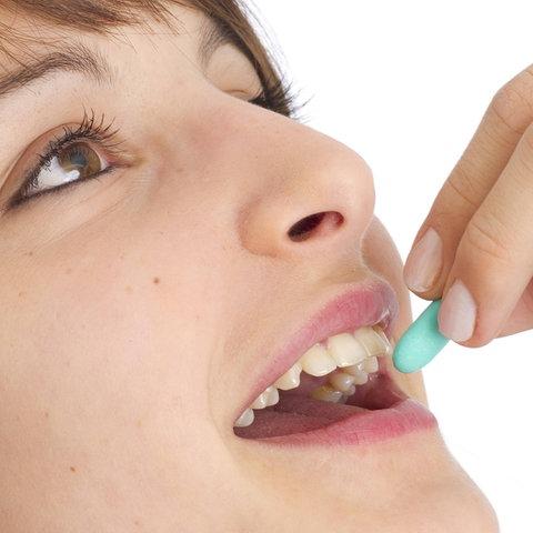 Eine Frau schluckt eine Tablette