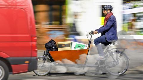 Ein Mann fährt auf einem Lastenrad durch die Stadt, an ihm vorbei zieht ein Abgas ausstoßendes Auto.
