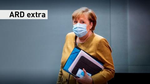 Angela Merkel mit Maske und Akten unter dem Arm.