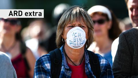 """Frau mit Mundschutz mit """"Ich bin dagegen""""-Aufschrift"""
