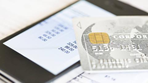 Handy mit offener Banking-App und Bankkarte darüber gelegt.