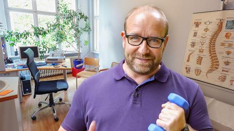 Oberarzt Mario Berwald kümmert sich um eine Patientin mit Rückenschmerzen.