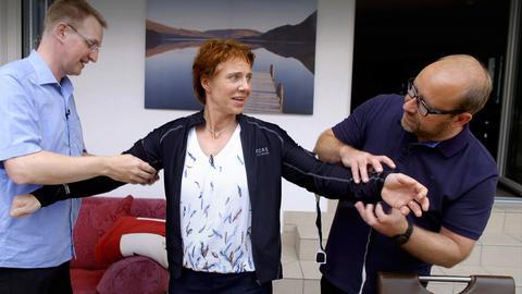 Dr. Berwald und ein Kollege legen der Protagonisten ein Bandscheiben-Druckmessungs-Anzug an