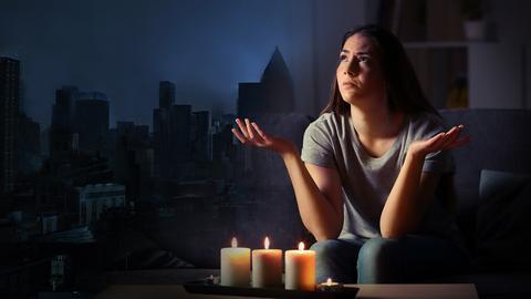 Blackout in Hessen - Eine Frau sitzt bei Kerzenschein - in Frankfurt gibt es einen Stromausfall