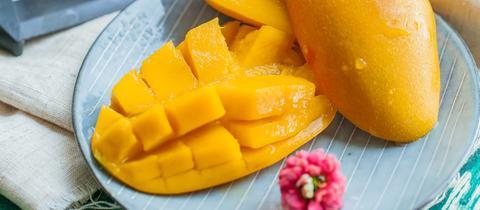 Aufgeschnittene Mangos liegen auf einem bunten Teller.