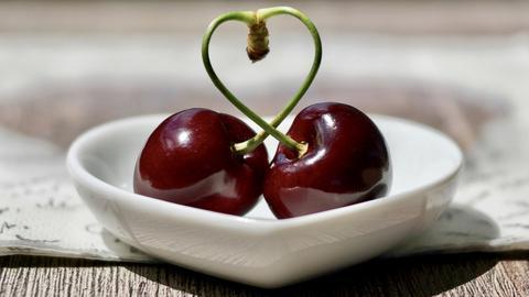 Zwei Kirschen, dessen Stiele miteinander verbunden sind und eine Herzchenform bilden.
