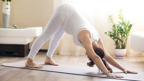 Eine schwangere Frau macht eine Yogaübung.