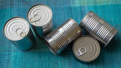 Fünf Konservendosen unterschiedlicher Größe liegen oder stehen auf blauem Stoffgrund.