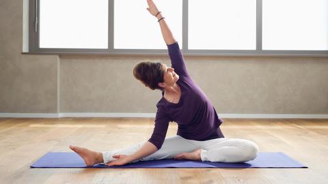 Eine Person sitzt auf einer Matte und macht eine Übung.
