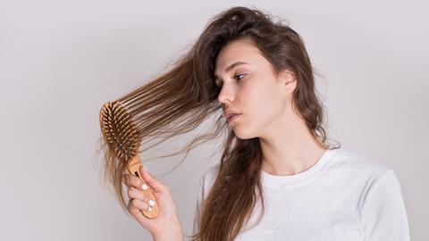 Eine junge Frau bürstet ihr strohiges Haar.