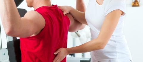 Eine Person macht Übungen für den Rücken auf einem Gerät. Eine andere Person unterstützt sie.