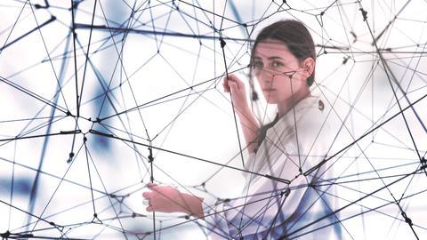 Eine Frau gefangen in einem Spinnennetz aus Fäden.