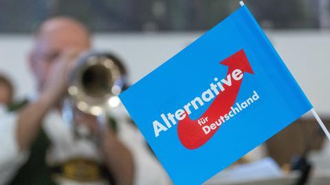 Ein Fähnchen der AfD vor einem Trompeter in Tracht.