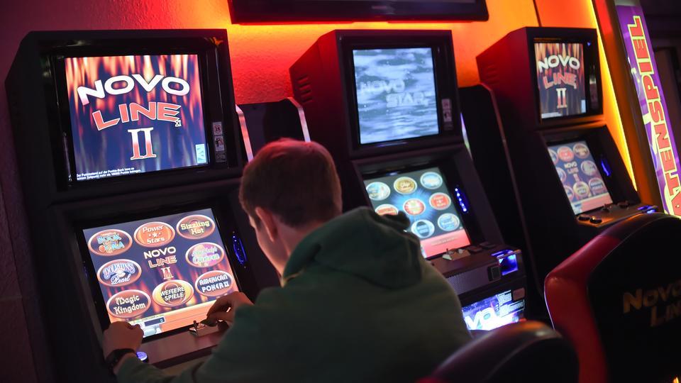 Ein junger Mann spielt in einem Casino an einem Spielautomaten.
