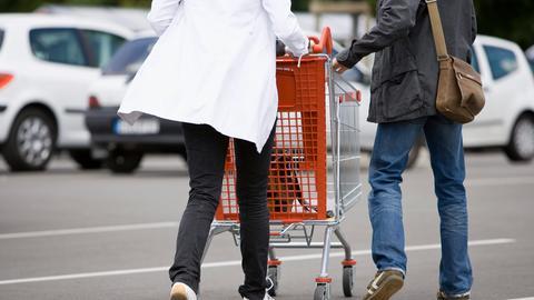Ein Paar schiebt einen Einkaufswagen über den Parkplatz eines Supermarktes.