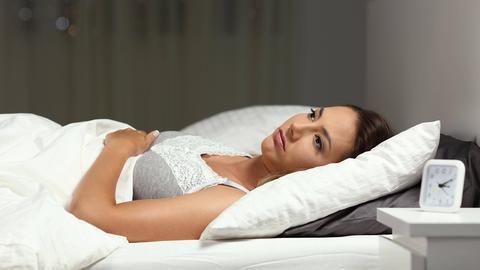 Eine Frau liegt wach im Bett