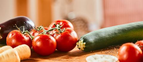 Eine Zucchini und ein Tomatentstrauch liegen auf einer Holzunterlage.