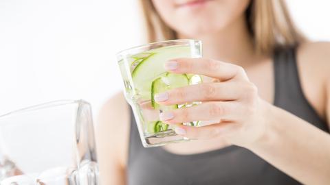 Eine Persion hält ein Glas mit Wasser und Gurken.