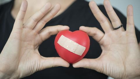 Eine Frau hält einen herzförmigen Gummiball, der mit einem Pflaster beklebt ist, in den Händen vor der Brust.